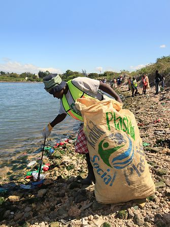 Woman collecting plastic waste on beach in Haiti